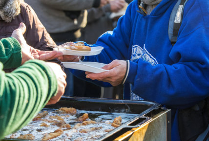 giving a meal to the person wearing a blue jacket