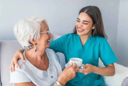 Happy senior woman talking with friendly nurse at geriatric ward