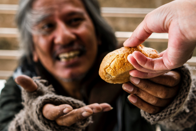 hand giving bread or food to happy face homeless male